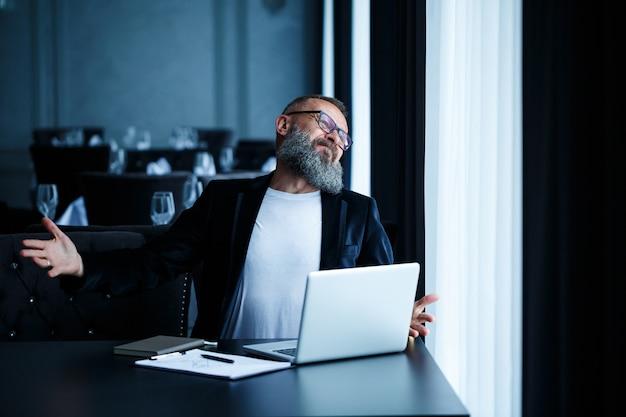 Взрослый бизнесмен мужского пола работает над новым проектом и смотрит на графики роста акций. сидит за столом у большого окна. смотрит на экран ноутбука и улыбается