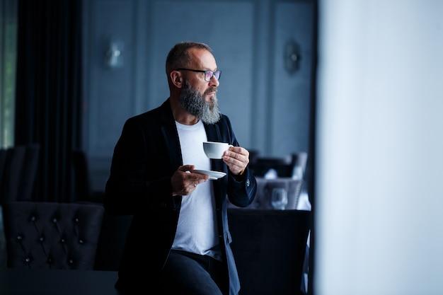 Взрослый мужчина-наставник, директор, бизнесмен в очках и костюме пьет кофе и отдыхает. концепция рабочего дня
