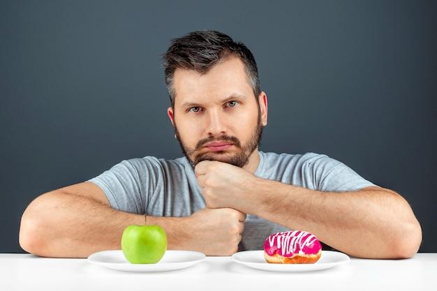 成人男性は、ドーナツと青リンゴから選択します。誘惑、ファーストフード、健康食品、ダイエット、ボディケアに対する概念の抵抗。