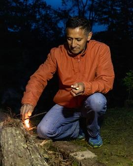 森の真ん中で夜にキャンプファイヤーを照らす大人の男