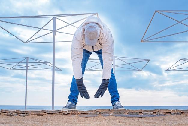 Взрослый мужчина выполняет физические упражнения на пляже в холодное время года
