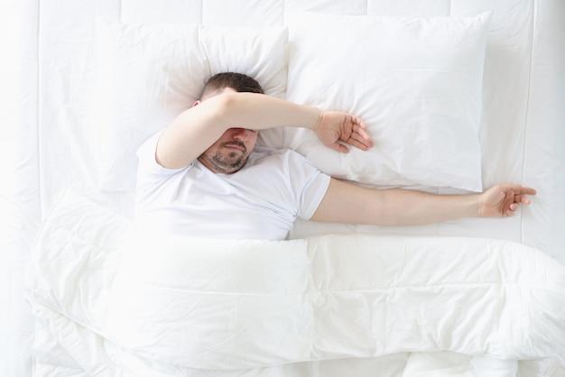大人の男性が大きなベッドの寝室で寝る