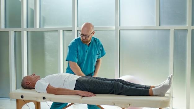 成人男性は、現代のリハビリクリニックで専門の医師と一緒に筋力を鍛えています...