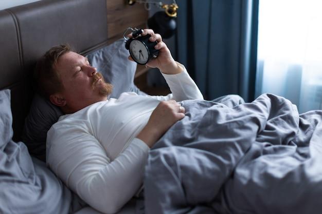 한 성인 남자가 집에 있는 침실에 있는 침대에 있는 알람 시계에 눈을 뜨고 자기가 늦잠을 자서 알람을 깨고 싶다는 사실에 매우 놀라고 속상해합니다