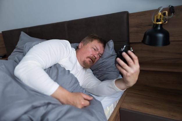 성인 남자는 집 침실에 있는 침대에 있는 알람 시계에 눈을 뜨고 자기가 늦잠을 잤다는 사실에 매우 놀라고 속상합니다