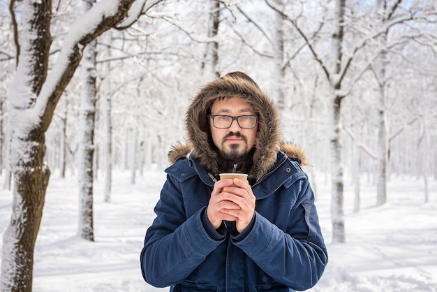 頭にフードと毛皮が付いたアノラックジャケットを着た成人男性。冬と霜のテーマ。彼の手に紙コップでコーヒーやお茶。氷点下の日の白人ハンサムな男の肖像画。