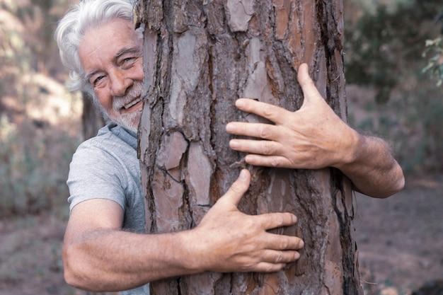 수염과 흰 머리카락을 가진 성인 남자가 숲에서 나무 줄기를 껴안으 며 미소를 지었다. 지구의 날 개념. 함께 우리는 삼림 벌채로부터 지구를 구합니다