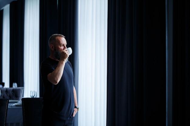 수염을 기른 성인 남자가 커피를 마시고 창밖을 내다본다. 근무일 필드 레크리에이션 개념