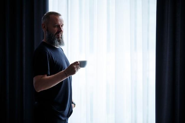 Взрослый мужчина с бородой пьет кофе и смотрит в окно. концепция отдыха в поле рабочего дня