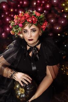 Сидит взрослая пухлая женщина в образе ведьмы с цветами на голове
