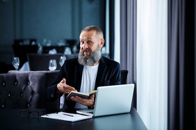 Взрослый успешный бизнесмен мужского пола работает над новым проектом и смотрит на графики роста в блокноте. сидит за столом у большого окна. смотрит в блокнот и улыбается