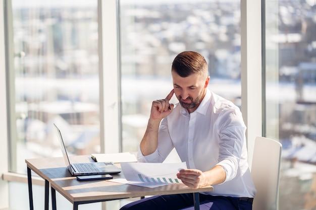 성공한 성인 남성 사업가는 큰 창문이 있는 사무실에 앉아 노트북에서 일하며 새로운 프로젝트를 진행합니다.