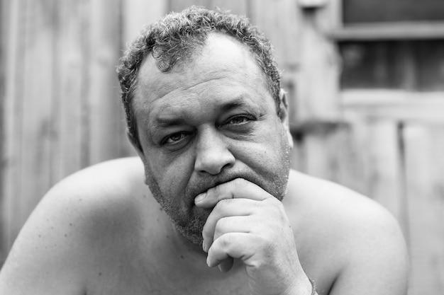 村の家の中庭で裸の胴体を持った大人の無精ひげを生やした男性のアルコール依存症。閉じる。黒と白の写真。