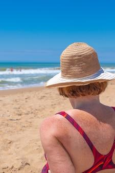 Взрослая женщина в купальнике и шляпе сидит на берегу моря в солнечный день, вид сзади. летние каникулы, путешествия и туризм.