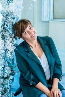 Взрослая женщина сидит возле елки и улыбается