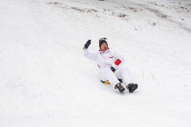 大人の女性が山から氷そりに乗る。感情的に。冬の楽しみ。あらゆる目的のために。