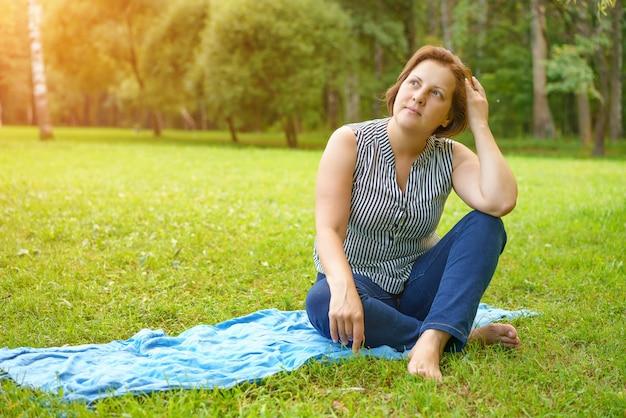 晴れた夏の日に公園の緑の芝生のマットの上に座っている大人の女性
