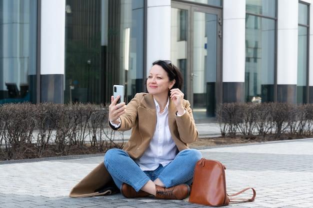 大人の女性が歩道に座って、嬉しそうな表情でビデオリンクを介して話します。