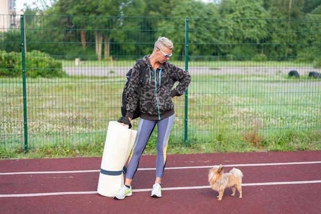 성인 여성이 작은 개와 함께 경기장에서 훈련합니다. 어떤 목적을 위해.