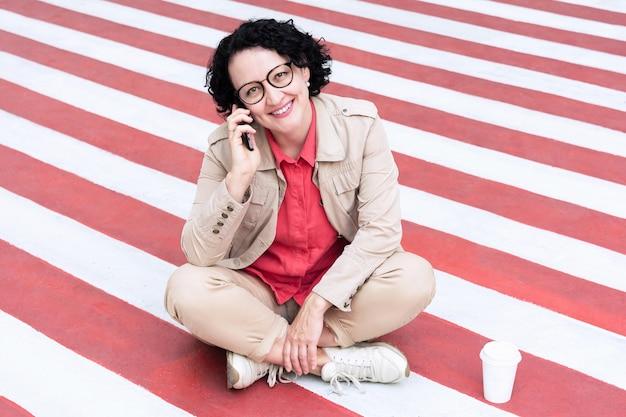眼鏡をかけた大人の女性が歩道に座って、笑顔で電話で話している