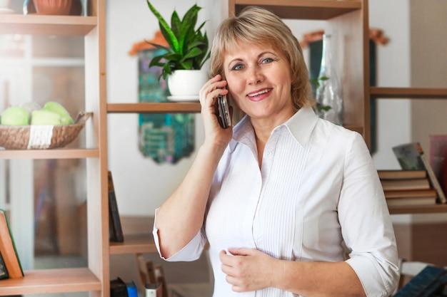 Взрослая женщина, работающая на ноутбуке в офисе