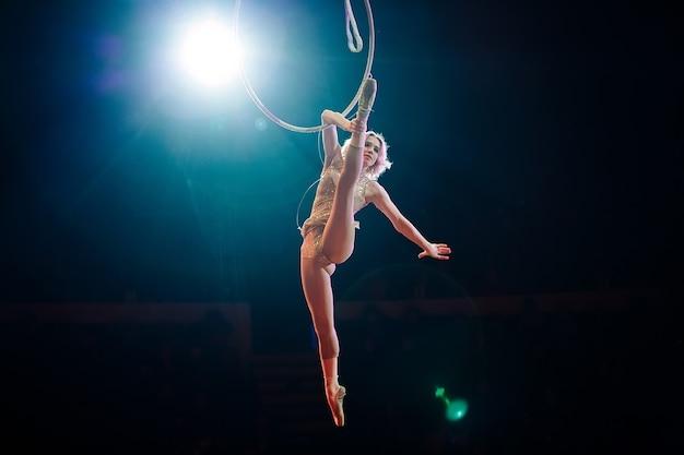 Воздушная гимнастка показывает выступление на арене цирка.