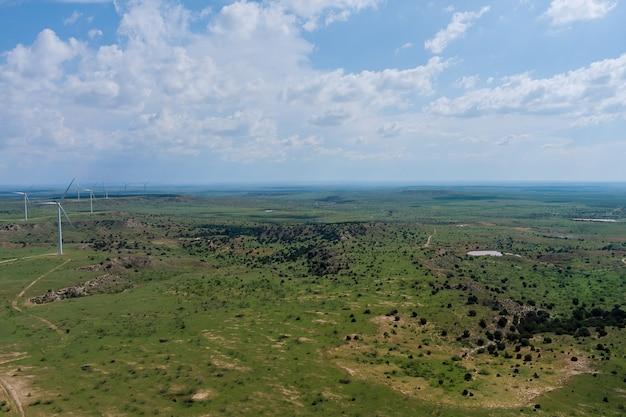 丘のあるテキサスの風景の中の空中パノラマビュー風力エコエネルギータービン