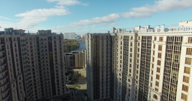 대형 현대식 주거용 건물과 그 뒤에 있는 햇살 가득한 도시 경관의 조감도