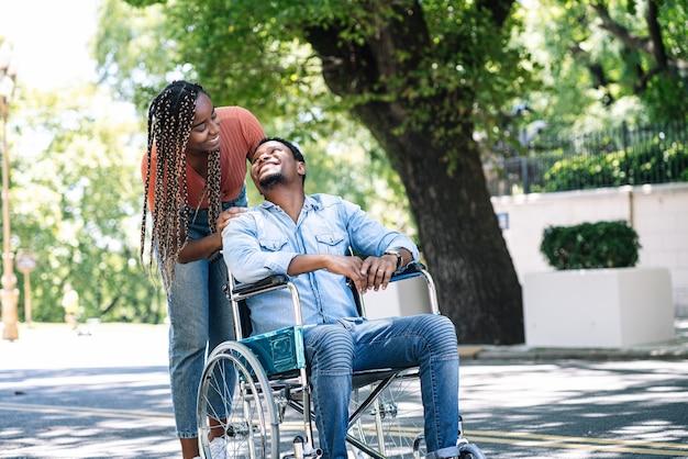 彼のガールフレンドと屋外の散歩を楽しんでいる車椅子のアフリカ系アメリカ人の男性。
