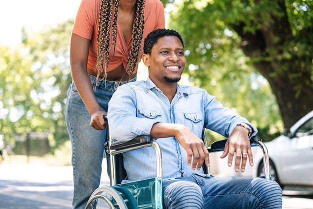 彼のガールフレンドと屋外散歩を楽しんでいる車椅子のアフリカ系アメリカ人の男