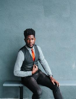 Афро-американский мужчина в жилете сидит на скамейке и моделирует
