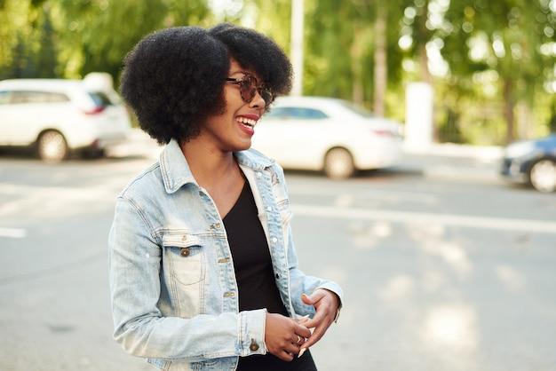 アフリカ系アメリカ人の女性がサングラスをかけた街の通りに立って笑います。
