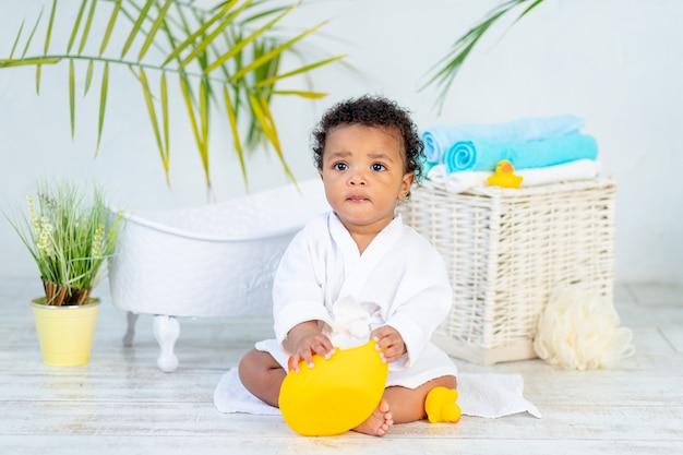 목욕과 목욕 후 흰 코트를 입은 아프리카 아기는 어린 아이들의 보살핌과 위생의 개념인 집에서 오리와 놀고 있습니다.