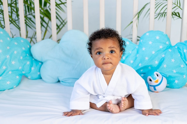 목욕과 목욕 후 흰 가운을 입은 아프리카 아기는 어린 아이들의 보살핌과 위생의 개념인 잠자리에 들기 전에 집에서 침대에 앉아 있습니다.
