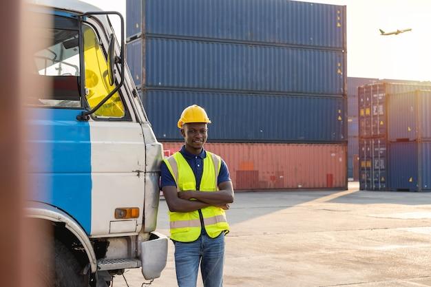Африканский водитель грузовика отдыхал и счастливо улыбался возле грузовика. на контейнерном складе