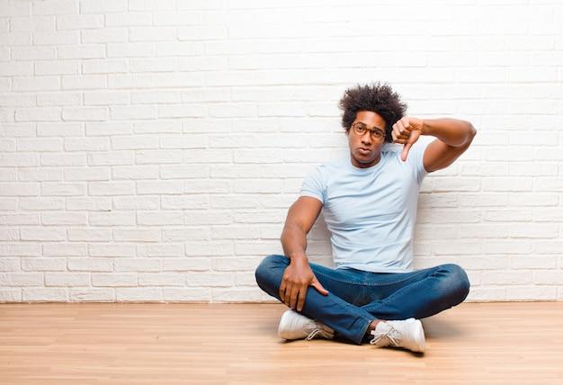 Афроамериканский парень сидит, показывает палец вниз с серьезным взглядом