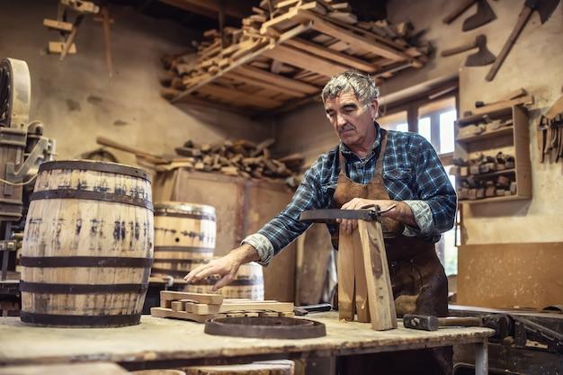 나이 든 장인이 빈티지 작업장에서 나무 통을 만듭니다.