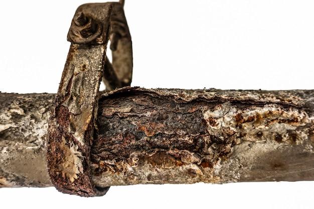 매달린 지지대가있는 오래된 녹슨 파이프 라인