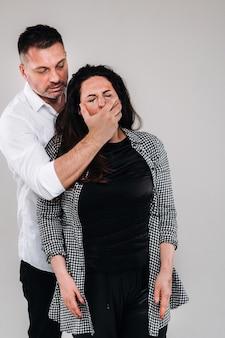 공격적인 남자는 구타당한 여자가 비명을 지르지 못하도록 입을 막는다. 가정 폭력.