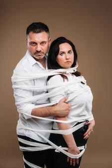 공격적인 남자는 구타당한 여자를 껴안고 함께 붕대로 싸여 있습니다. 가정 폭력
