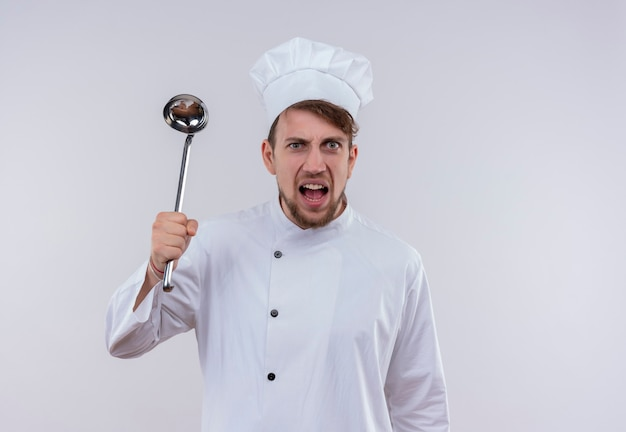 Агрессивный молодой бородатый шеф-повар в белой униформе держит черпак и смотрит на белую стену