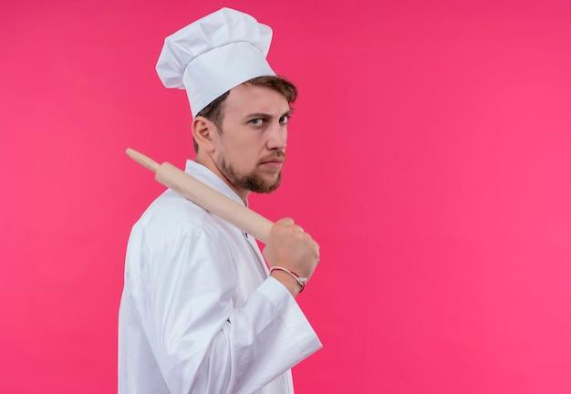 ピンクの壁を見ながらめん棒を保持している白い制服を着た攻撃的な若いひげを生やしたシェフの男