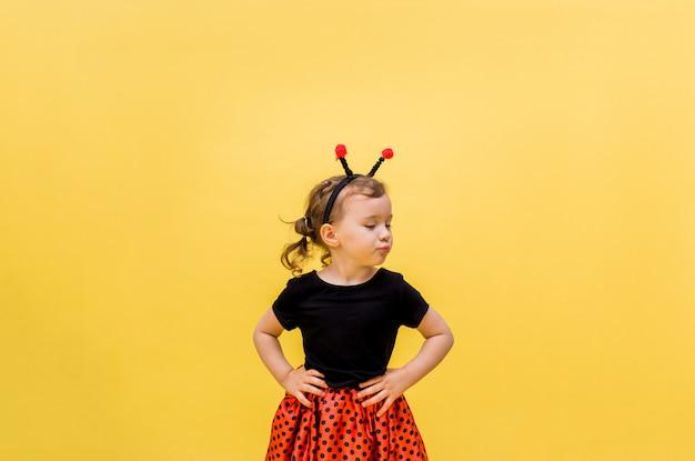 Несчастная маленькая девочка в костюме божьей коровки на желтом фоне