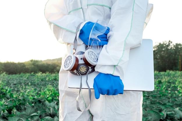 Агроном, одетый в белый защитный костюм, маску и синие перчатки, держит ноутбук на фоне поля с урожаем. проблемы концепции химикатов и пестицидов.