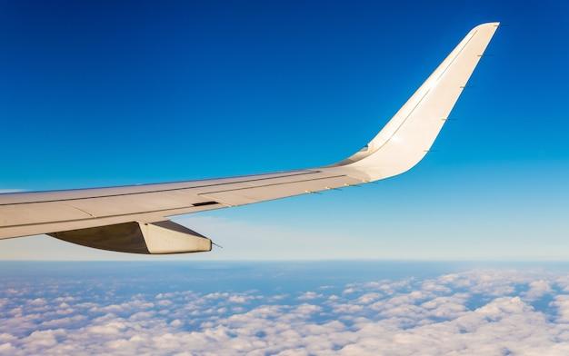 雲の上を空を飛ぶ航空機の翼