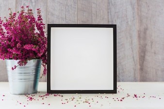 An aluminum pot with pink flowers and white square shape photo frame on table