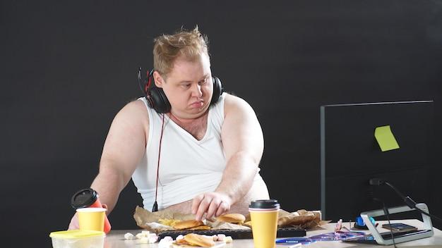 Tシャツを着た驚くほどの肉付きの良い男が、コンピューターのすぐそばに座って、孤立した黒い背景を食べる