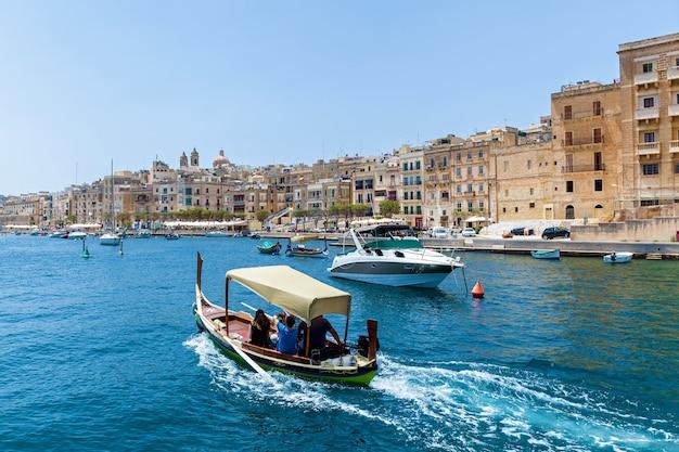 ヨーロッパのマルタの夏の晴れた日に古い建物の背景に伝統的なマルタのボートで素晴らしい海の景色。