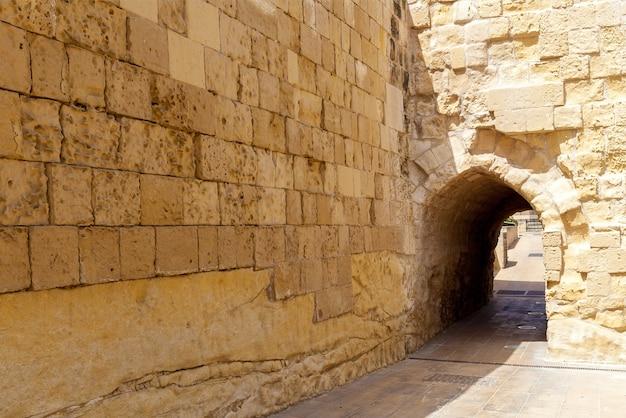Удивительный вид на средневековую каменную крепость с красивыми зелеными насаждениями на мальте.