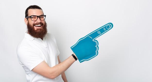 Удивительно счастливый бородатый мужчина улыбается в камеру, держа синюю веерную перчатку, указывая ею на свободное место